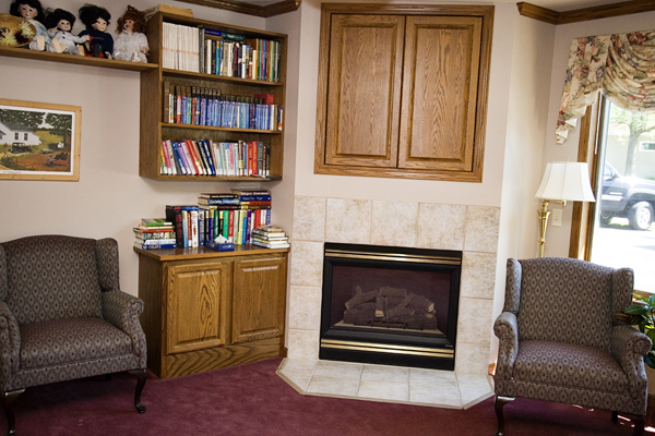 Residents sitting room with fireplace and library